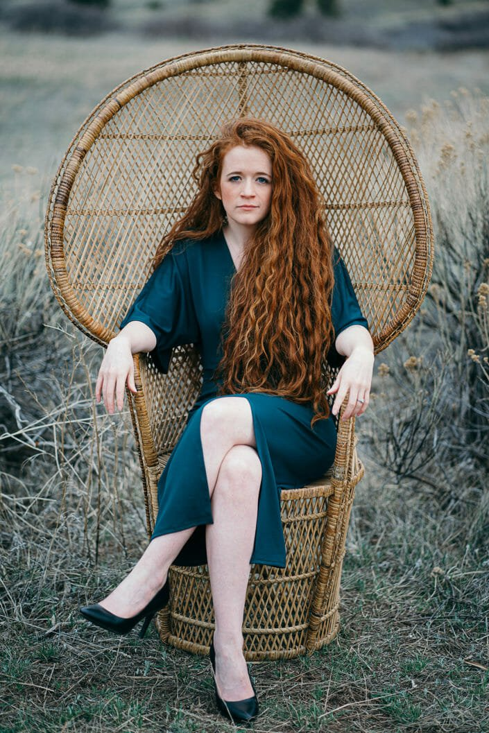 bohemian artistic shot of red head in peacock chair at red rocks in denver, colorado