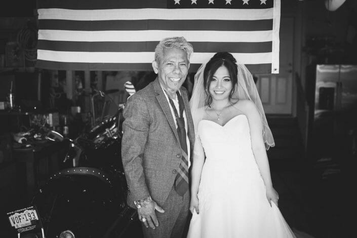 Bride with uncle underneath american flag with motorcyle