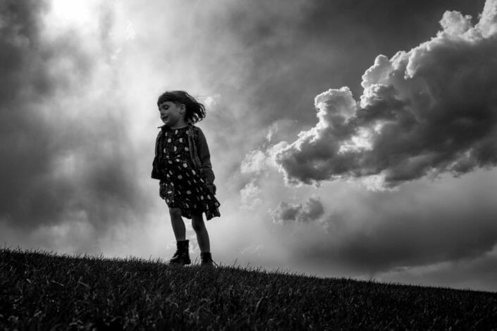candid artistic shot of little girl in dramatic clouds