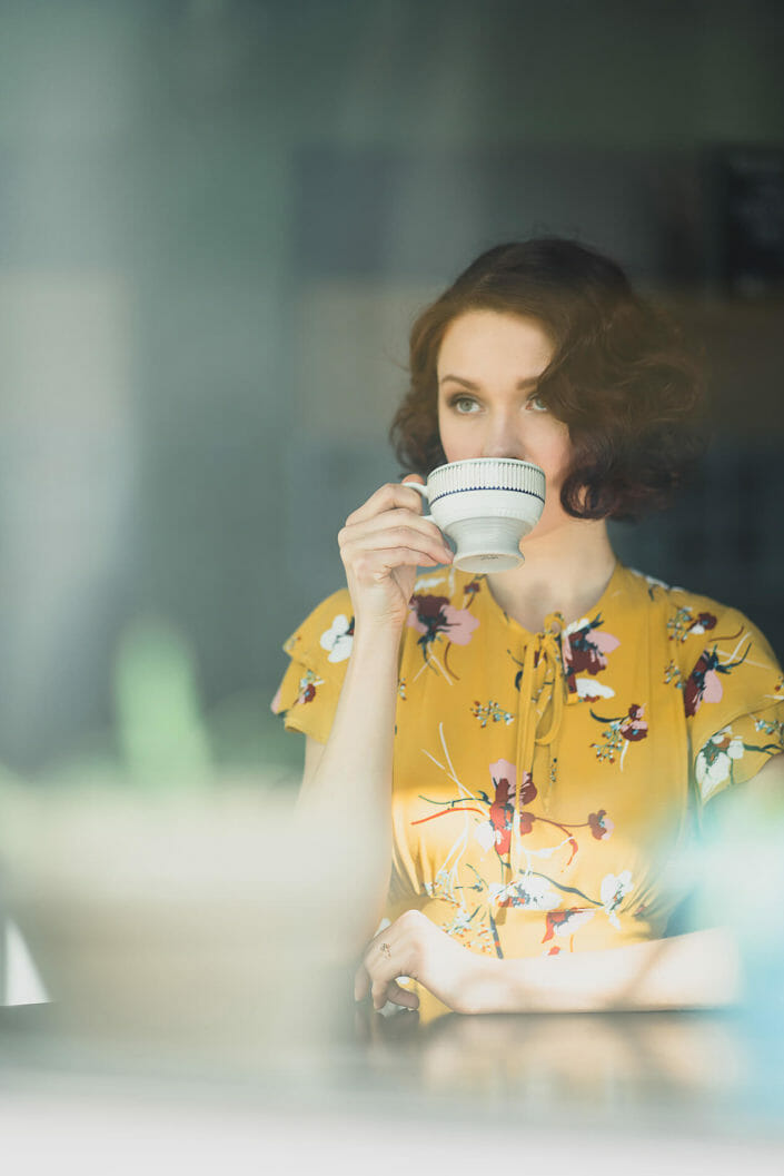 Fashion Photography - Model in window with coffee cup